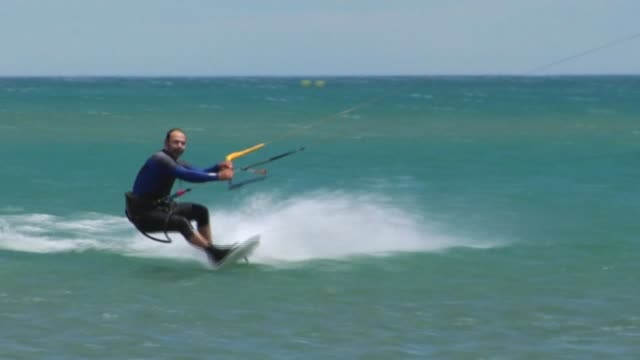 after waiting patiently for the past three months kitesurfing enthusiasts waste no time heading back to the beach and leaping back onto their boards... - aude stock videos & royalty-free footage