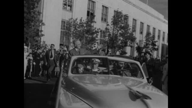 after winning the election, u.s. president harry truman waves to spectators during a motorcade in washington d.c. - 1948年点の映像素材/bロール