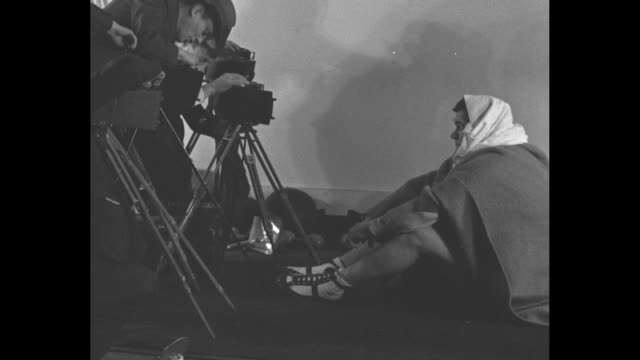 After working out Babe Ruth sits on floor of trainer Artie McGovern's gym wrapped in blanket and his head wrapped in towel in front of cameramen...