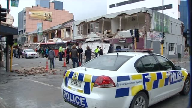 aftermath of central city near hagley park with partially crushed car damaged turret police car in front of commercial buildings with collapsed front... - christchurch stock-videos und b-roll-filmmaterial