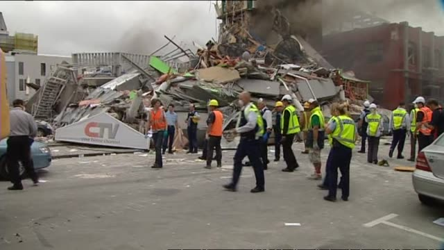 aftermath of destruction of smoking canterbury television building with rescue workers and police standing around - christchurch stock-videos und b-roll-filmmaterial