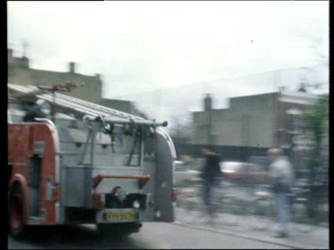 vídeos de stock e filmes b-roll de aftermath of riots fire engines pass burnt out buildings firemen with hoses police with incident tape brixton riots; apr 81 - 1981