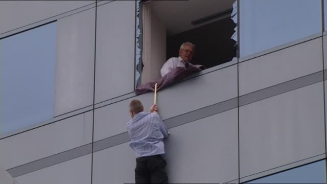 aftermath rescue of office workers from building with man abseiling outside window police officer instructing rescue of people from forsyth barr... - christchurch stock-videos und b-roll-filmmaterial