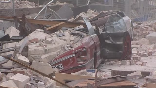 aftermath with crushed cars on side of road on gloucester street outside winnie bagoes red brick building, group of men clearing rubble from car and... - christchurch stock-videos und b-roll-filmmaterial