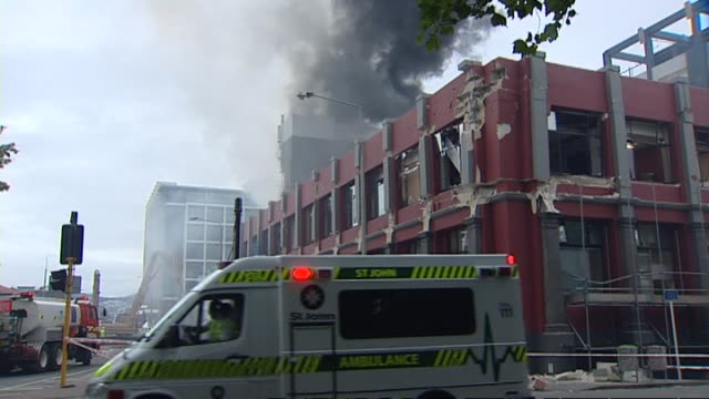 aftermath with smoke rising from site of badly damaged ctv building and police and st john ambulance staff assisting injured victims in temporary... - christchurch stock-videos und b-roll-filmmaterial