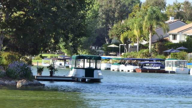 afternoon westlake village lake people out on the lake in pontoon boats houses on the lake shore with docks and boats westlake village a small... - westlake village california stock videos & royalty-free footage