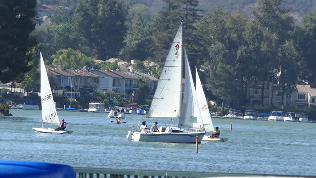 afternoon westlake village lake small dinghies racing pontoon boat and a canoe in the background westlake village a southern california city in los... - westlake village california stock videos & royalty-free footage
