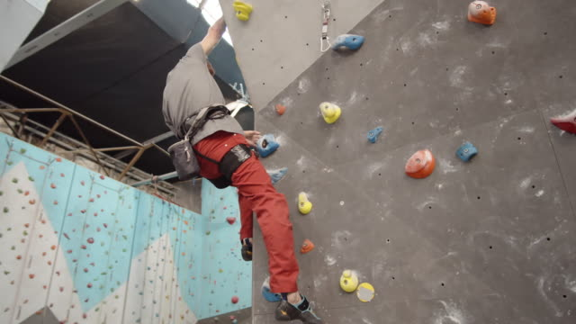 Aged Climber Practicing Bouldering in Gym