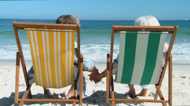 ms aged couple looking at ocean sitting on beach chairs / cape town, western cape, south africa - deckchair stock videos & royalty-free footage