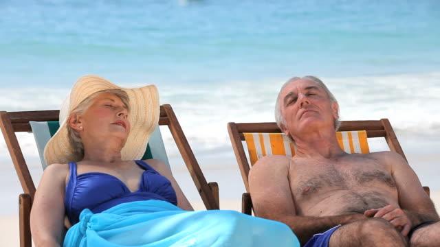 vídeos de stock, filmes e b-roll de ms aged couple relaxing on beach chairs on beach / cape town, western cape, south africa - espreguiçadeira