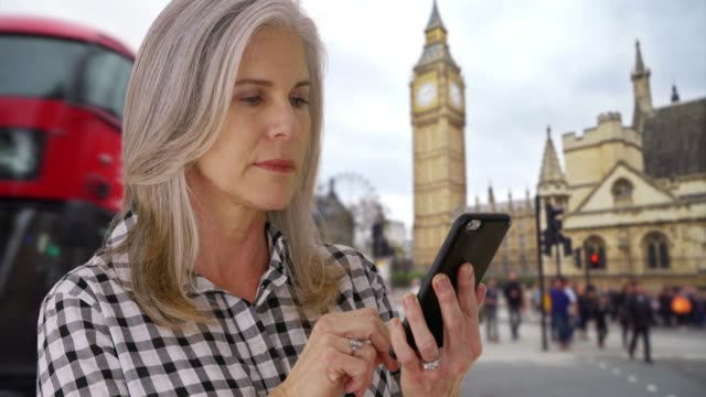aged woman in london uses smartphone in front of big ben - big ben点の映像素材/bロール