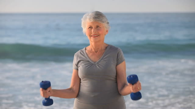 MS Aged woman working on muscles with dumbbells on beach / Cape Town, Western Cape, South Africa