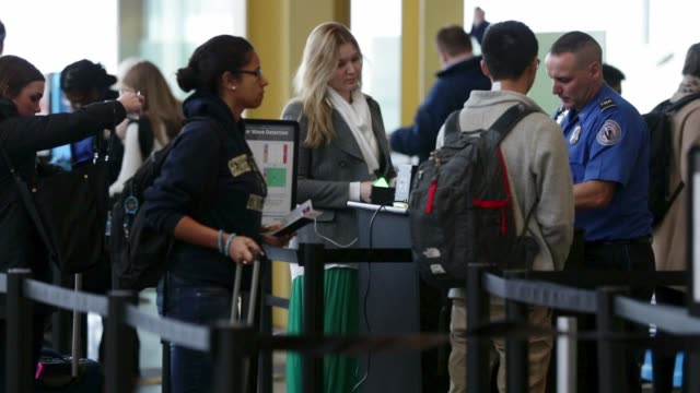 a tsa agent check id of travelers at a security check point at ronald reagan washington national airport on the day before thanksgiving which is... - aeroporto nazionale di washington ronald reagan video stock e b–roll