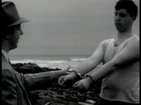 vidéos et rushes de fbi agent handcuffing prisoner ms agent shaking undercover man's hands nyc - 1942