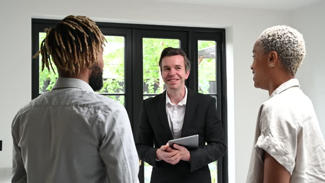 agent interacting with prospective buyers in home interior - selling stock videos & royalty-free footage