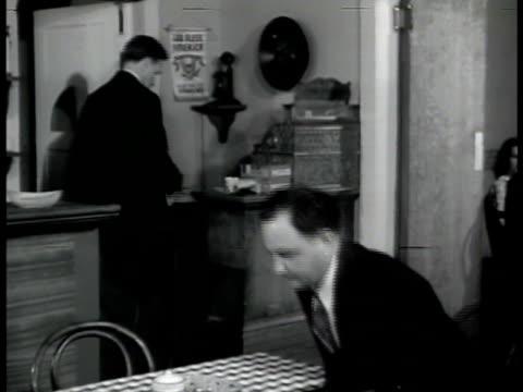 Agent 'Miller' in crowded restaurant taking seat asking to speak to Nazi member 'Baumeyer' VS Miller amp Baumeyer talking at table sliding aspirin...