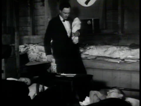 vidéos et rushes de agent sneaking by two sleeping germans in cellar ms agent switching bag on chair int ms fbi agents checking contents of bag in office vs pulling... - 1942