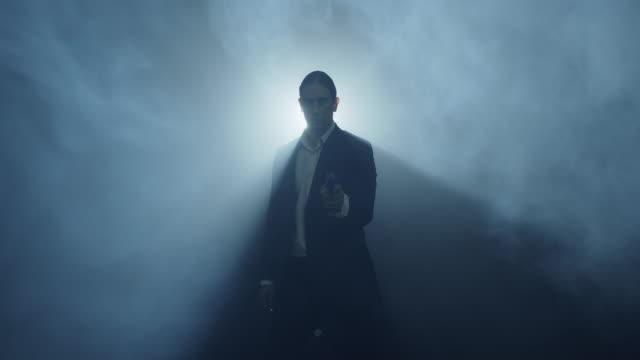 エージェントは煙の中を歩き、彼のピストルを描きます。 - order点の映像素材/bロール