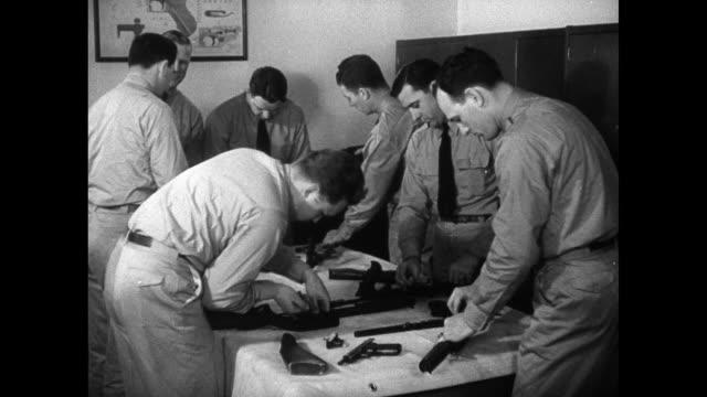 agents assembling rifle, hand guns on table. fbi agents practice japanese martial arts jiu-jitsu, disarming partner & knocking man off feet to mat,... - fbi video stock e b–roll