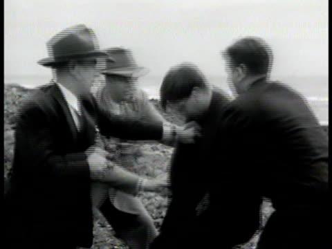 Agents capturing escaped Nazi prisoner by bushes coastal shoreline BG wrestling prisoner to ground MS Undressing prisoner VS Undercover agent putting...