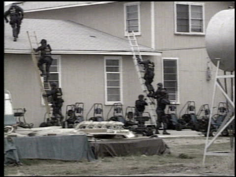 fbi agents climbing ladders outside mount carmel center with branch davidians inside / atf agents firing handguns into building / atf agent on roof... - cult stock videos & royalty-free footage