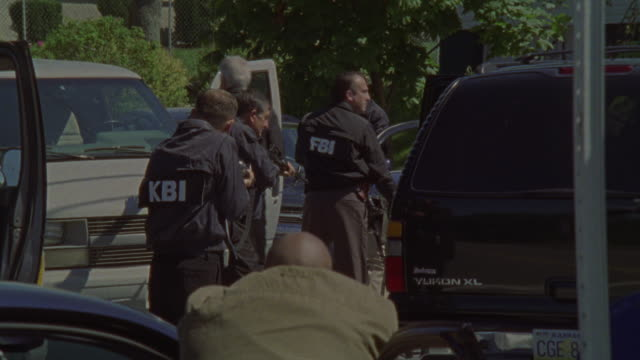 FBI agents surround a van with guns drawn.