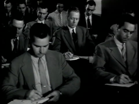Agents taking notes at desks CU Board of 'Nazi Party' tree stemming from photograph of Adolf Hitler MS Agent at file cabinets MS Pulling out file...