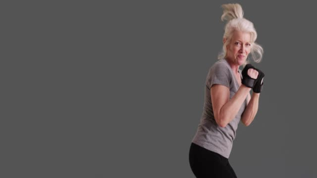 stockvideo's en b-roll-footage met aggressive mature woman shadowboxing kicking at screen in studio in slowmo - schoppen lichaamsbeweging