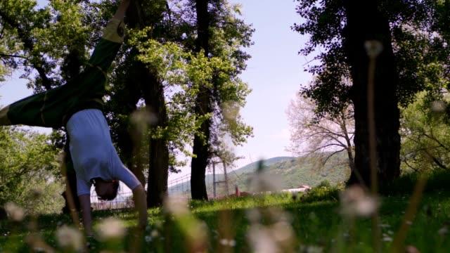 stockvideo's en b-roll-footage met behendige jonge vrouw die cartwheels in zonnig park praktizert - flexibiliteit