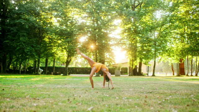 ms agile young woman practicing front flips in sunny park - cartwheel stock videos & royalty-free footage