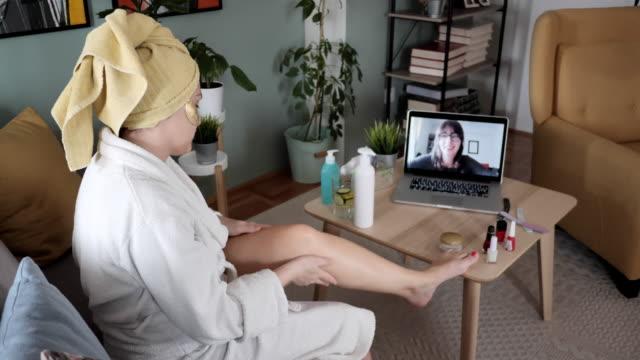 vídeos y material grabado en eventos de stock de mujer envejecida que aplica crema hidratante en su piel durante la videollamada con un amigo - personas bellas