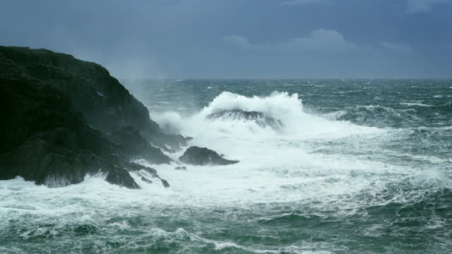 WS SLO MO agitated waves breaking on rocky shore with stormy weather and wind / Lewis Island, Scotland, United Kingdom