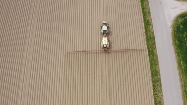 vídeos de stock, filmes e b-roll de campo agrícola sendo pulverizado na primavera - pulverizando