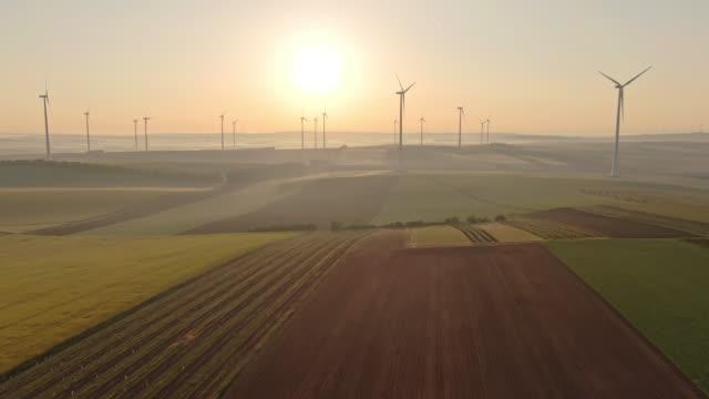 vídeos y material grabado en eventos de stock de aerial campos agrícolas rodeados de aerogeneradores - multicóptero