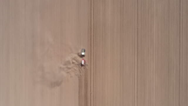 agriculture aerial, tractor with harrow prepares large field for planting crop - farm stock videos & royalty-free footage