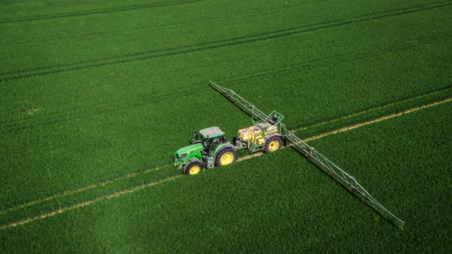 aerial: agriculture - crop sprayer tractor - spraying stock videos and b-roll footage