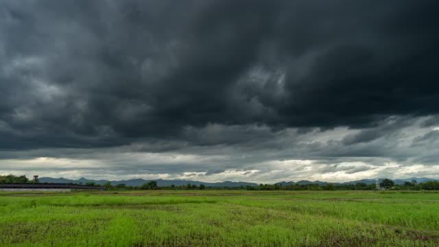 vidéos et rushes de champ d'agriculture et nuages de tempête se déplaçant le time lapse de coucher du soleil. - ciel changeant