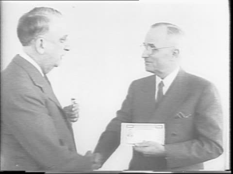 agriculture secretary ezra benson and president harry truman pose for photographers with small document / truman gives benson one dollar and receives... - financial accessory stock videos & royalty-free footage