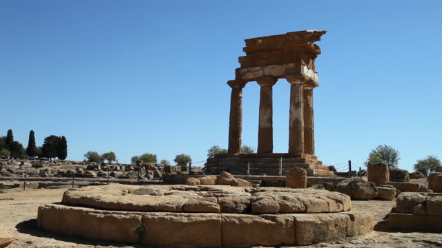 vidéos et rushes de agrigento, in the foreground a circular altar of the sanctuary of the cathonic divinities, in the background the temple of castor and pollux - archéologie