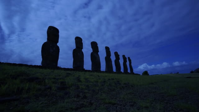 Ahu Akivi Moai statues are silhouetted above an Easter Island shoreline.