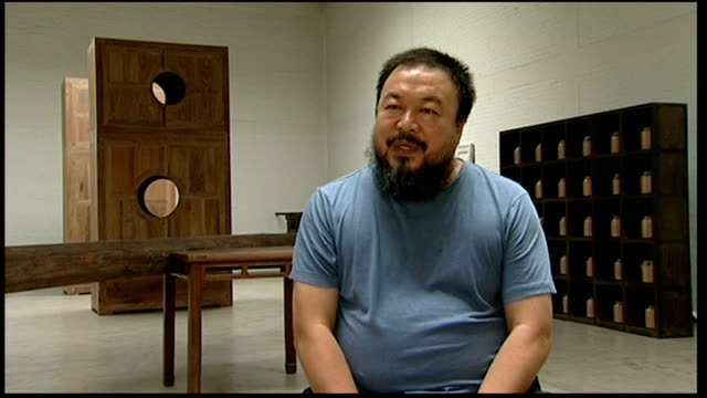 ai weiwei stadium brochure being looked at ai weiwei interview sot - limited freedom of speech, individual human rights are not fully exercised... - bird's nest stock videos & royalty-free footage