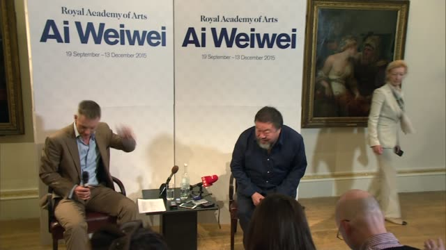 Ai Weiwei urges British government to do more to help refugees INT Ai Weiwei into room for press conference Ai Weiwei taking seat TV crews Ai Weiwei...
