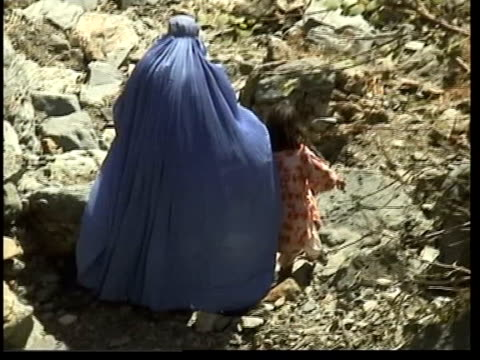 aid agencies call for pause in the bombings; itn pakistan: ext women refugees in full islamic dress walking along rocky hillside woman and child... - ceasefire stock videos & royalty-free footage