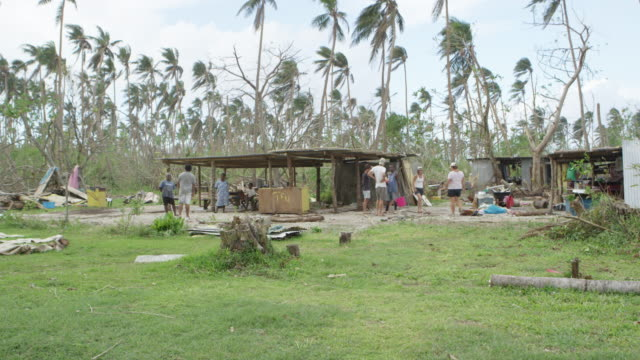 vanuatu - march 31, 2015: aid workers and locals talk next to shacks - pazifikinseln stock-videos und b-roll-filmmaterial