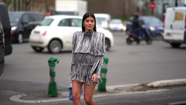 stockvideo's en b-roll-footage met aida domenech wears a black and white fringed turtleneck dress, a blue balmain bag, silver bejeweled shoes, outside balmain, during paris fashion... - zoom out