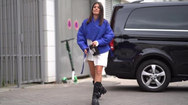 stockvideo's en b-roll-footage met aida domenech wears a blue jacket a white dress black boots outside ann demeulemeester during paris fashion week womenswear spring summer 2020 on... - modeweek