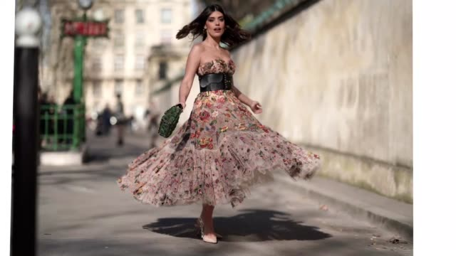 Aida Domenech wears a lace pleated dress with colored embroidered flowers a black large leather belt a green bag Lady Dior outside Dior during Paris...