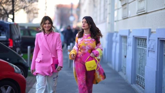 vídeos de stock, filmes e b-roll de aida domenech wears a pink and yellow msgm top, a colorful knit coat, hot pink crop pants, a yellow bag, white heeled mules ; angela rozas saiz wears... - rosa cor