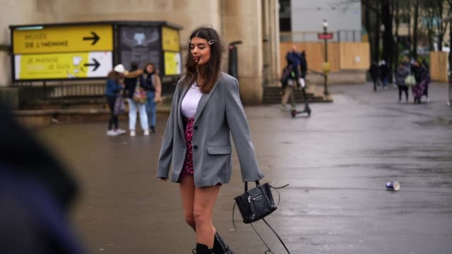 aida domenech wears hair pins, a gray oversized jacket, a white t-shirt, a pink floral print skirt, a black leather bag, black leather boots, outside... - skirt stock videos & royalty-free footage