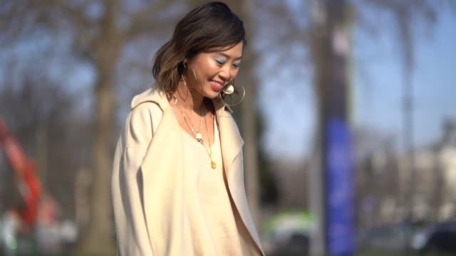Aimee Song wears a beige coat a beige dress during Paris Fashion Week Womenswear Fall/Winter 2018/2019 on February 28 2018 in Paris France